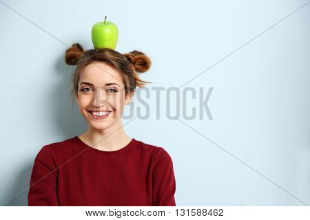 Portrait of young woman with apple on head against blue wall background