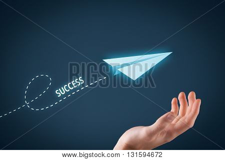 Success concept. Paper plane representing dreaming about success and hand touching this dream comes true.