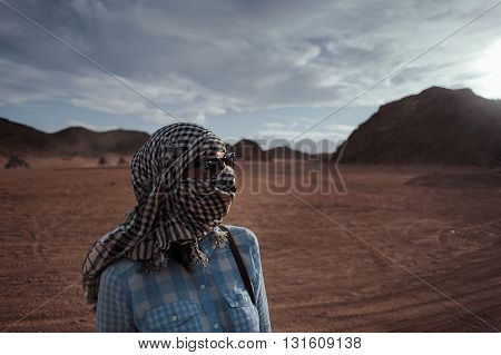 In the desert with kaffiyeh on face