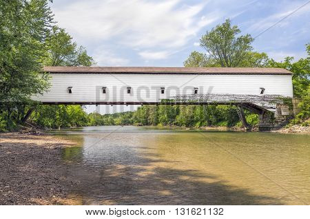 Built in 1861 the white Jackson Bridge crossing Sugar Creek in rural Parke County Indiana is the longest single span covered bridge in the state.