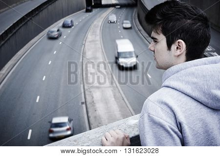 Depressed Young Man Contemplating Suicide On Road Bridge