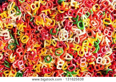 DETAIL OF COLORFUL PASTA LETTERS HEAP AT MARKET