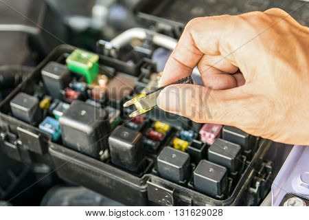 Auto mechanic checking a car fuse. car, fuse, automotive, electronics, box,