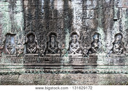Detail of a stone carved wall in Angkor temples complex Siem Reap Cambodia