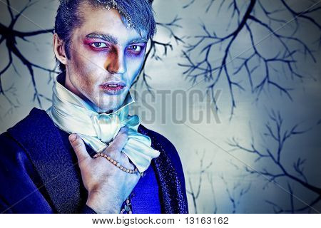 Portrait of a handsome young man with vampire style make-up. Shot in a studio. poster