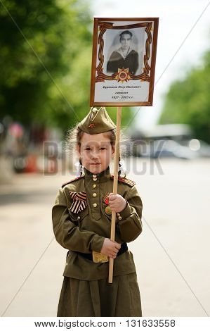 Orel Russia - May 9 2016: Celebration of 71th anniversary of the Victory Day (WWII). Girl with poster her great-grandfather on Immortal regiment marching vertical