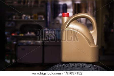 Golden plastic canister on a tire in a dark background