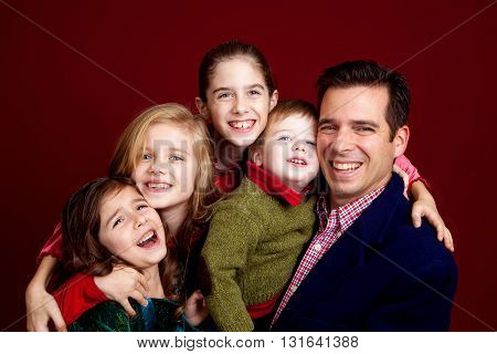 A good looking father poses with his four kids on a red background.  They are hugging in tight and the youngest girl is a bit squished and has a complaining face.