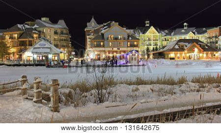 COLLINGWOOD, ONTARIO - JAN 22, 2016. A popular ski chalet resort in Collingwood known as Blue Mountain Village architecture lit up at night with frozen skating pond.