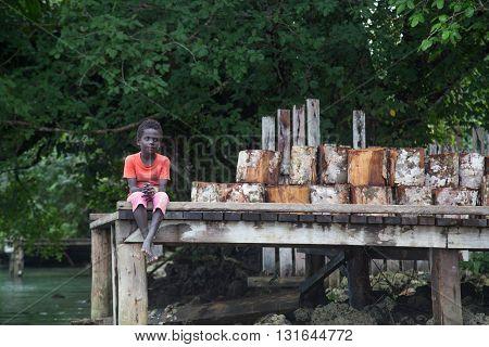 Seghe, Solomon Islands - June 16, 2015: Local boy sitting on a pier