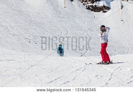 Young skier woman taking a photo with mobile phone