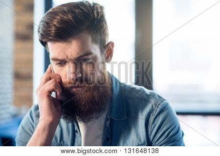 Out of temper. Moody handsome bearded man holding cell phone and  talking on it while feeling cheerless