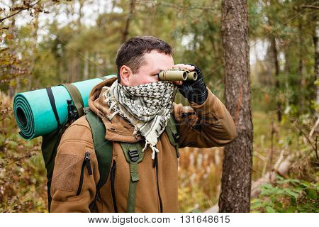 Man with binoculars at a deep forest.