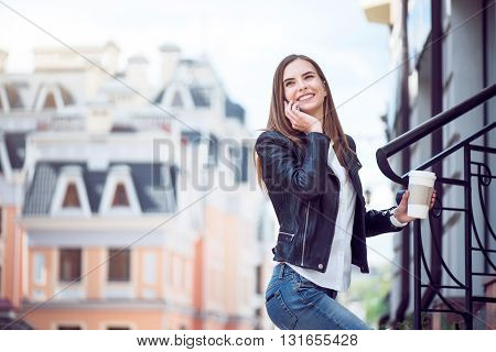 Glad to hear it.  Smiling and happy young woman speaking per cell phone and holding a cup of coffee while being in a big city and standing near stairs with big buildings in a background