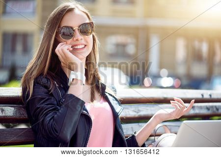 Listening. Smiling and cheerful young woman speaking per mobile phone with her mum and using a laptop while sitting on a bench and being in a park