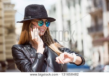 Waiting.  Smiling and cheerful modern young woman speaking per mobile phone with her friend, looking at her smart watch and waiting for her