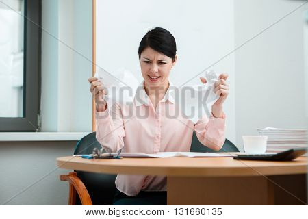 Woman in office with crumpled paper.