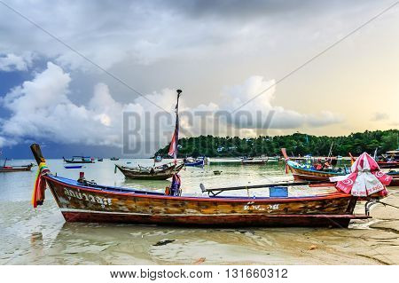 Rawai Thailand - August 25 2014: Traditional long-tail boats used for tourist trips & fishing moored in bay just before sunset at Rawai beach on southern tip of Phuket southern Thailand