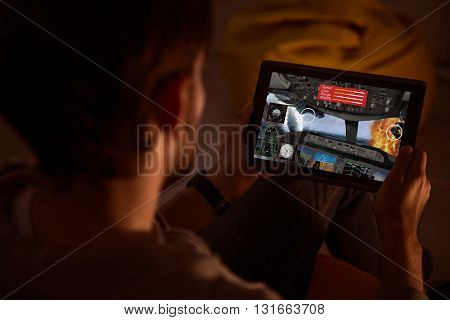 Some fun. Top view of a man holding a tablet and playing a videogame during the nighttime