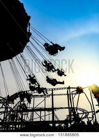 Silhouettes of people on a merry go round at sundown