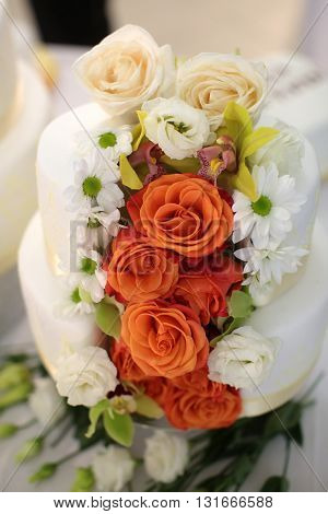 Wedding cake traditional multi level white beautiful decorated with roses and flowers on table background