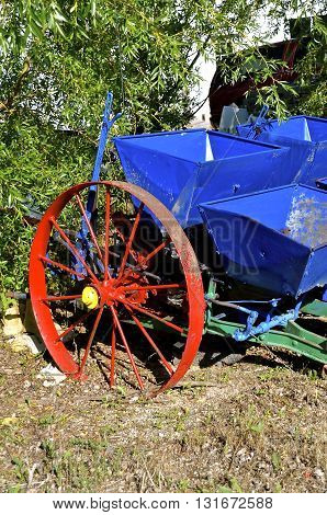 A very old potato planter with red steel wheels and blue holding boxes is refurbished.