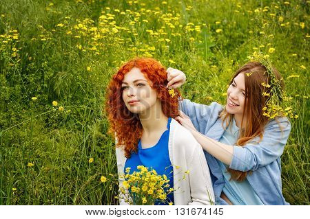 Best friends forever. Friends sitting on the grass in the park. BFF. Close friends. She weaves flower girlfriend hair.
