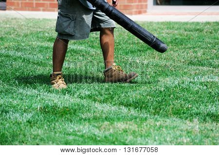 outdoor worker operates blower to clean the garden