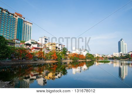 HANOI, VIETNAM, May 21, 2016: Hanoi street in summer with blooming flamboyant flowers near the lake