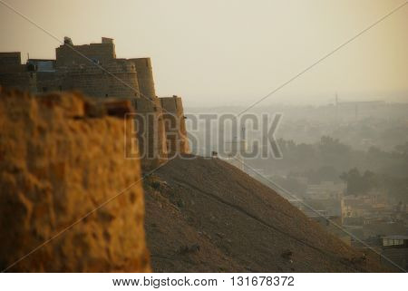 The magnificient stone walls of the fortress of Jaisalmer dominating the city at sunrise. Jaisalmer Rajasthan India