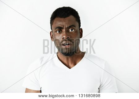 Headshot Of Puzzled Black Office Worker In White Polo Shirt Looking In Shock And Frustration At The