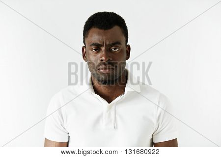 Portrait Of Angry Or Annoyed Young African American Man In White Polo Shirt Looking At The Camera Wi