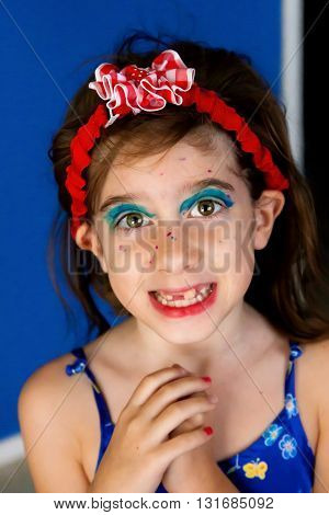 A girl who has given herself a makeover with magic markers smiles pleadingly at the camera with hands clasped and a hopeful smile.