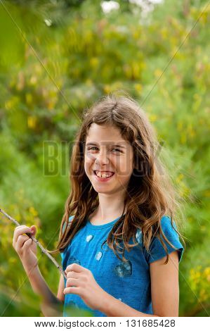 A laughing tween girl with messy hair stands with a stick in hand looking into the camera with a wrinkled nose and crooked teeth.