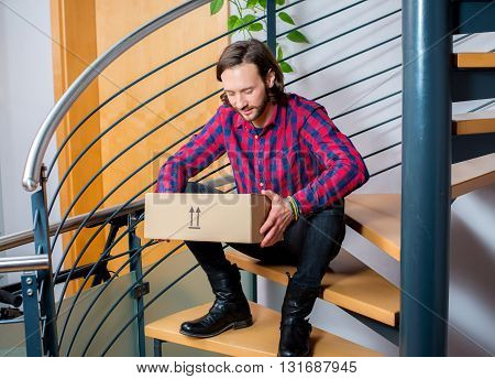Man Sitting In Corridor And Opening A Package