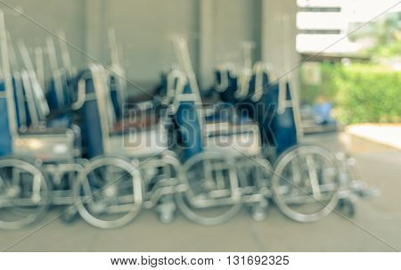 Blurred abstract background of row of Manual or self-propelled wheelchairs seating in hospital building interior
