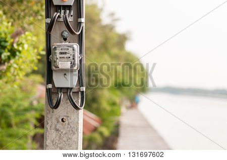 Electricity meter installed in the atmosphere of the waterfront in thailand