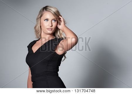 Portrait of beautiful blond model on grey background