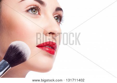 Close up of female face. Young attractive woman is applying powder on her cheek. She is looking forward with passion. Isolated and copy space in right side