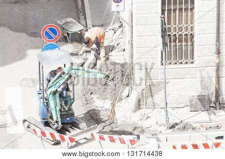 Udine , Italy - May 2 2016 : Sidewalk under construction curb and gutter installation in Construction workers.