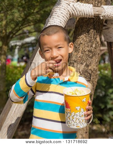 Asian boy eating eating popcorn with gusto.