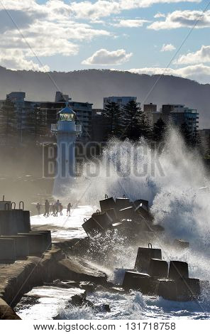 Big waves breaking over Wollongong harbor breakwall near the lighthouse