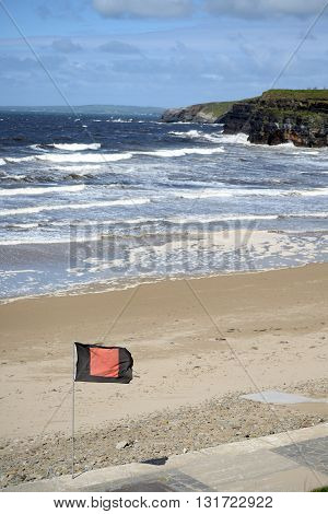 quicksilver flag flying beside surf school with ballybunionbeach and cliffs in background