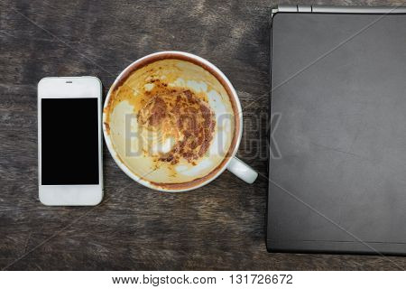 View from above with copy space wood table with laptop coffee and cellphone in latte art coffee shop