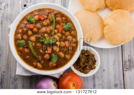 indian dish spicy Chick Peas also known as Chola Masala or Chana Masala or Chole served in a white bowl, isolated