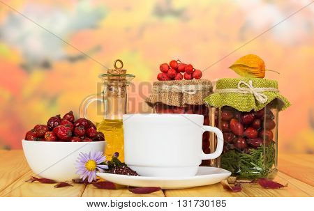 Banks with rowan berries, rose hips, a bottle of oil and a cup of tea in the background autumn leaves.