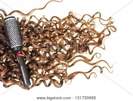 Brown ringlets and a round hairbrush isolated on white background.