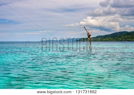Transparent sea dramatic sky traditional culture and green forest in the remote Malenge Beach Togean Islands Sulawesi Indonesia. poster