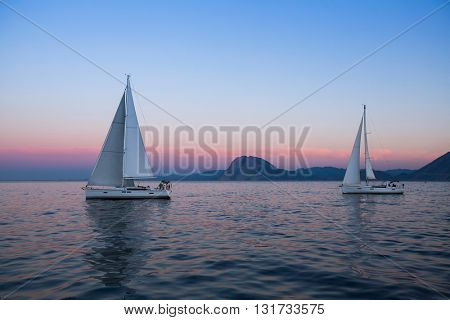 Sail boats near the rocky shores after amazing sunset.