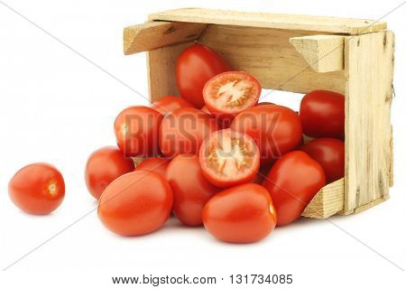 fresh and colorful italian roma tomatoes and a cut one in a wooden crate on a white background